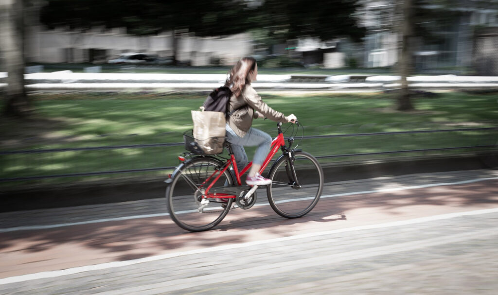 A woman cycling through the city on a red bike